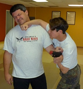 Master Strahan demonstrates a gun take-away technique to one of his students in the Krav Maga Class.